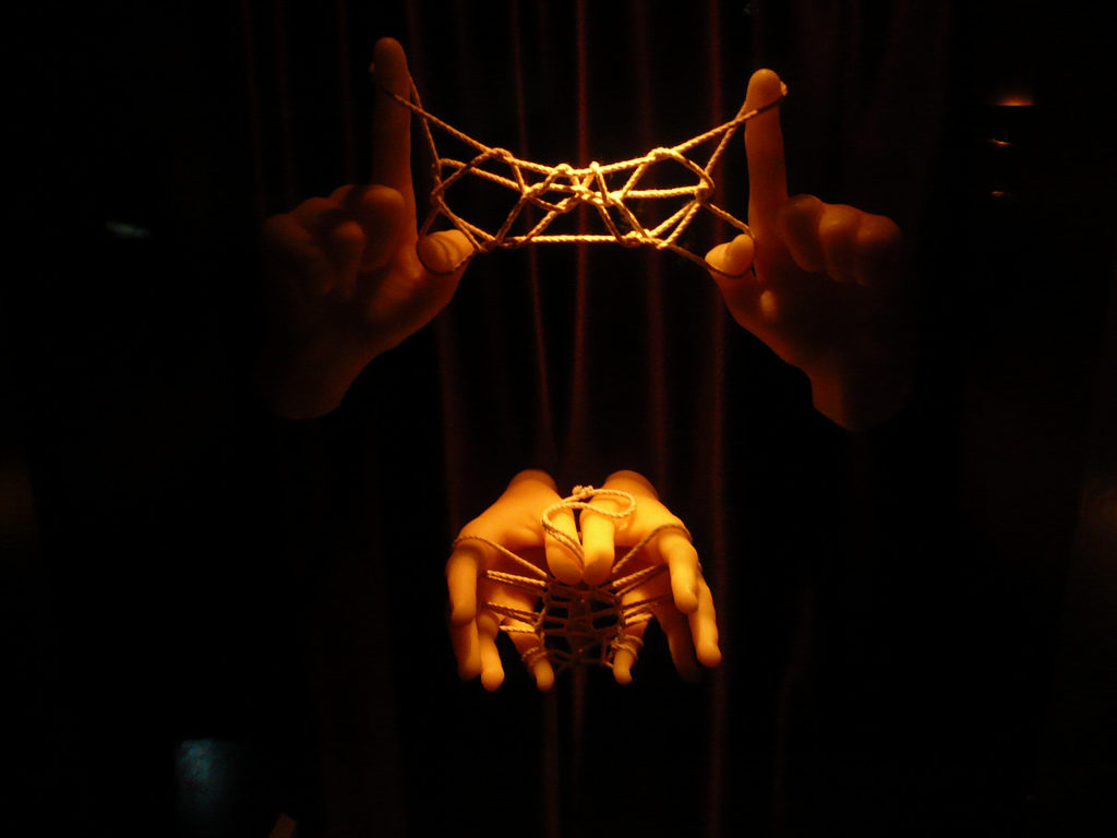 Four hands holding twisted ropes
