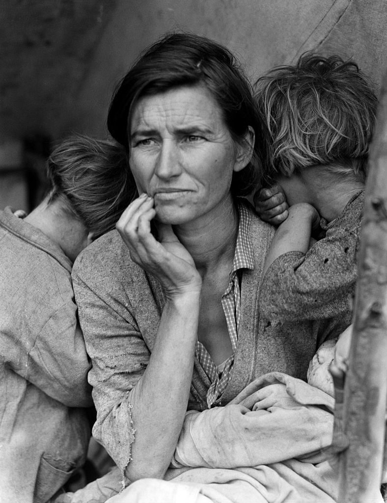 Migrant mother shelters children during the Great Depression
