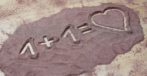 Picture of sand on the ground and someone wrote 1 + 1 = heart in it.